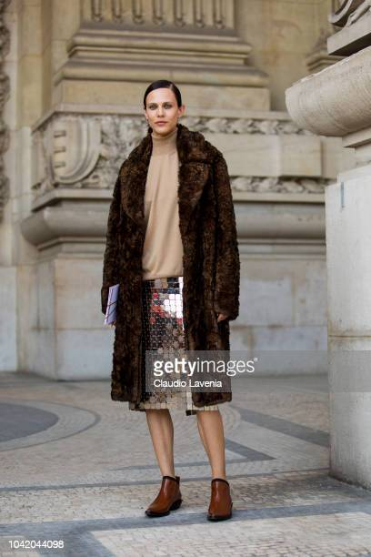 Aymeline Valade wearing a beige turtleneck sweater a sequin skirt brown boots and brown fur coat is seen before the Paco Rabanne show on September 27...