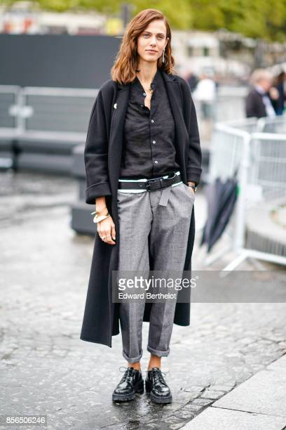 Aymeline Valade wears a black coat a black shirt gray pants black shoes and attends Le Defile L'Oreal Paris as part of Paris Fashion Week Womenswear...