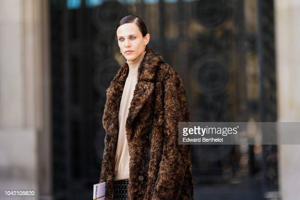 Aymeline Valade wears a brown faux fur coat a silver shiny skirt outside Paco Rabanne during Paris Fashion Week Womenswear Spring/Summer 2019 on...