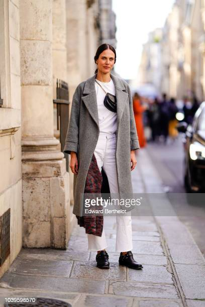 Aymeline Valade wears a gray coat a black bag a white tshirt white pants outside Jacquemus during Paris Fashion Week Womenswear Spring/Summer 2019 on...