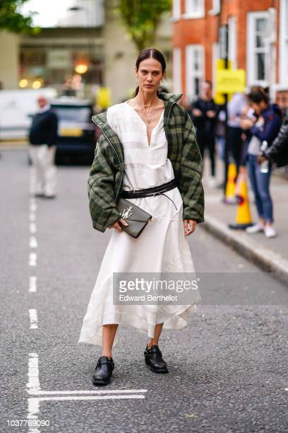 Aymeline Valade wears a green coat a white dress a JW Anderson bag during London Fashion Week September 2018 on September 15 2018 in London England