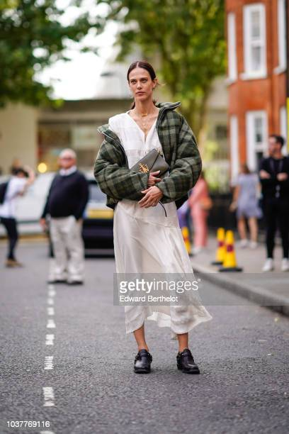 Aymeline Valade wears a green JW Anderson bag a green checked jacket a white dress during London Fashion Week September 2018 on September 15 2018 in...