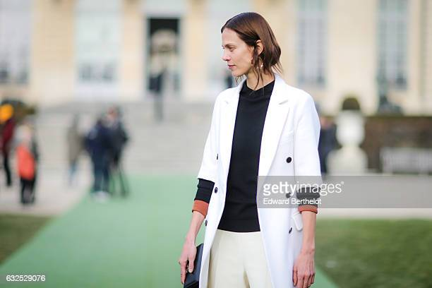Aymeline Valade wears a white jacket a black top white pants a black clutch and attends the Christian Dior Haute Couture Spring Summer 2017 show as...