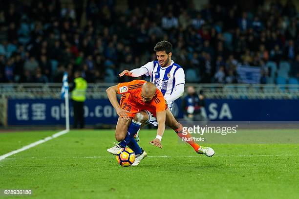 Aymen Abdennour of Valencia duels for the ball with Carlos Vela of Real Sociedad during the Spanish league football match between Real Sociedad and...