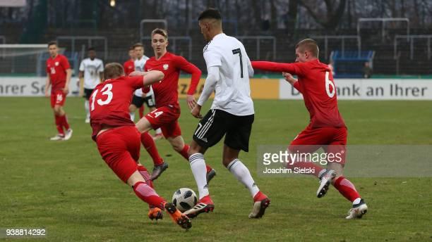 Aymen Barkok of Germany challenges Mateusz Spychala Marcin Listkowski and Maciej Palaszewski of Poland during the international friendly match...