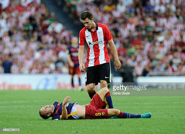 Aymeric Laporte of Club Athletic checks up on Andres Iniesta of FC Barcelona after Iniesta took a knock during the La Liga match between Athletic...