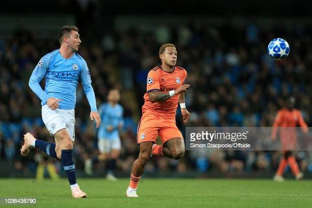 Aymeric Laporte of Man City and Memphis Depay of Lyon battle for the bouncing ball during the Group F match of the UEFA Champions League between...