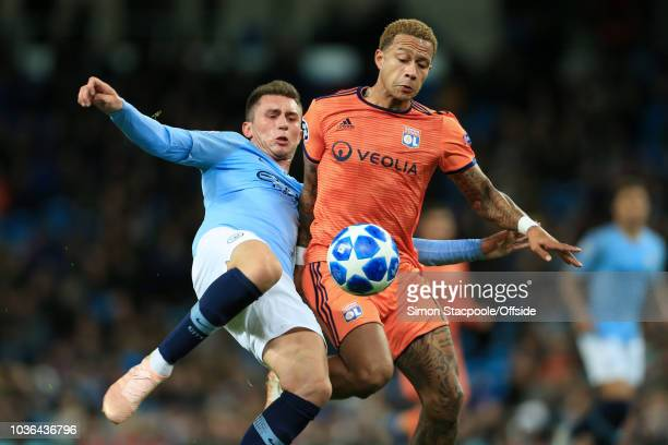 Aymeric Laporte of Man City battles with Memphis Depay of Lyon during the Group F match of the UEFA Champions League between Manchester City and...