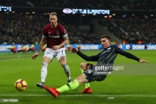 Aymeric Laporte of Manchester City attempts to keep the ball in play under pressure from Marko Arnautovic of West Ham United during the Premier...
