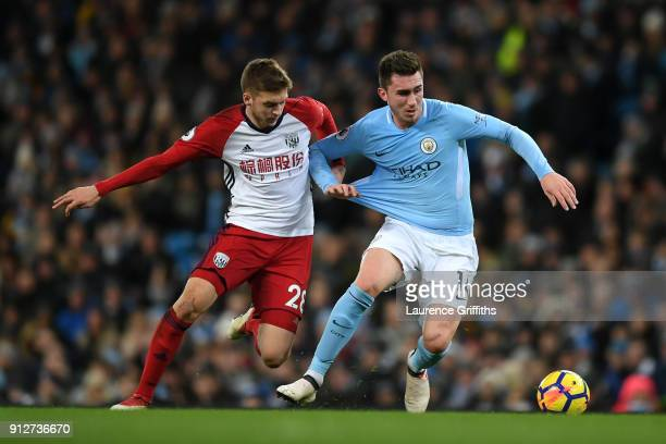 Aymeric Laporte of Manchester City is challenged by Sam Field of West Bromwich Albion during the Premier League match between Manchester City and...