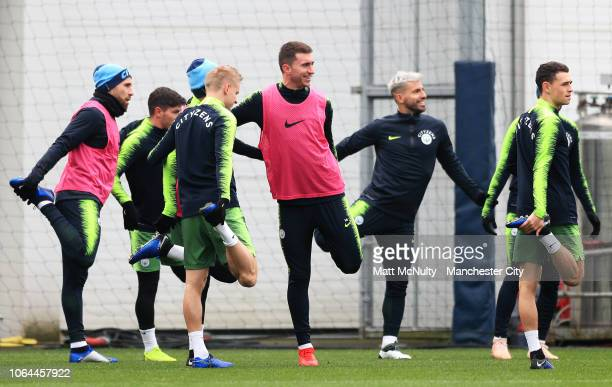 Aymeric Laporte of Manchester City stretches with teammates during a training session at Manchester City Football Academy on November 23, 2018 in...