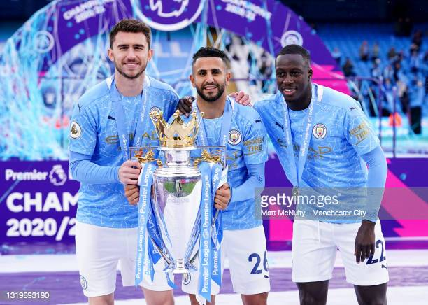 Aymeric Laporte, Riyad Mahrez and Benjamin Mendy of Manchester City celebrate with the trophy during the Premier League match between Manchester City...