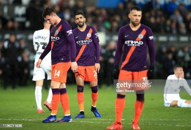Aymeric Laporte Riyad Mahrez and Nicolas Otamendi of Manchester City look dejected during the FA Cup Quarter Final match between Swansea City and...