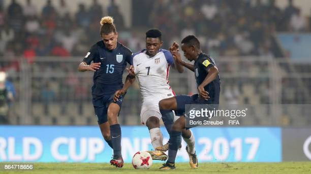 Ayo Akinola of the United States is challenged by Joel Latibeaudiere of England and Steven Sessegnon of England during the FIFA U17 World Cup India...