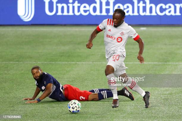 Ayo Akinola of Toronto FC dribbles past Andrew Farrell of New England Revolution to score a goal during the first half at Gillette Stadium on October...