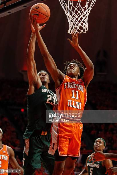 Ayo Dosunmu of the Illinois Fighting Illini shoots the ball as Xavier Tillman of the Michigan State Spartans defends from behind during the first...