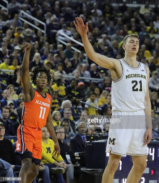 Ayo Dosunmu of the Illinois Fighting Illini watches his shot as Franz Wagner of the Michigan Wolverines reacts during the second half of the game at...