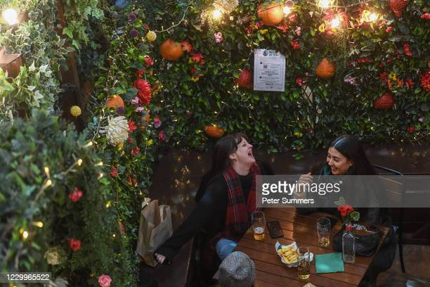Ayoung woman laughs while sat outside a pub in Covent Garden on December 5, 2020 in London, England. On Tuesday night, Dec 1, MPs voted in favour of...