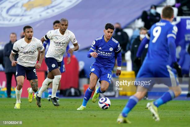Ayoze Perez of Leicester City runs with the ball as Gabriel Jesus and Fernandinho of Manchester City look on during the Premier League match between...