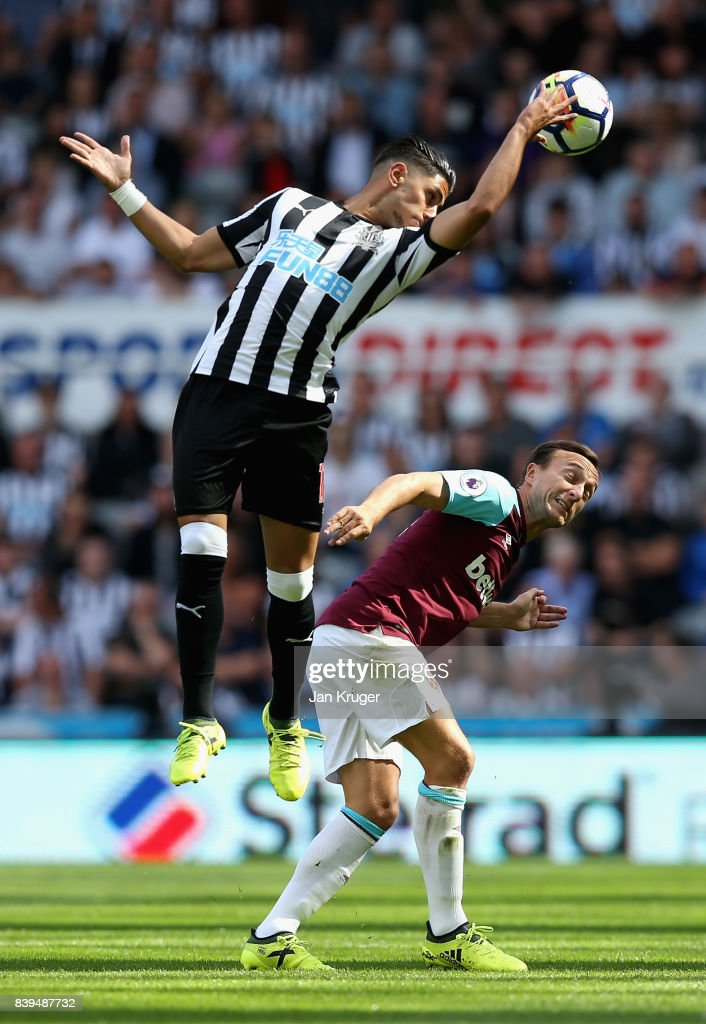 Ayoze Perez of Newcastle United and Mark Noble of West Ham United battle for possession in the air during the Premier League match between Newcastle United and West Ham United at St. James Park on August 26, 2017 in Newcastle upon Tyne, England.