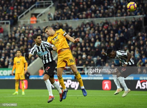Ayoze Perez of Newcastle United scores his team's first goal ahead of Conor Coady of Wolverhampton Wanderers during the Premier League match between...