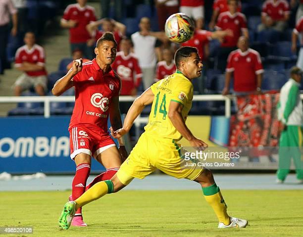 Ayron del Valle of America de Cali kicks the ball as Danny Cano of Bucaramanga defends during a match between America de Cali and Bucaramanga as part...