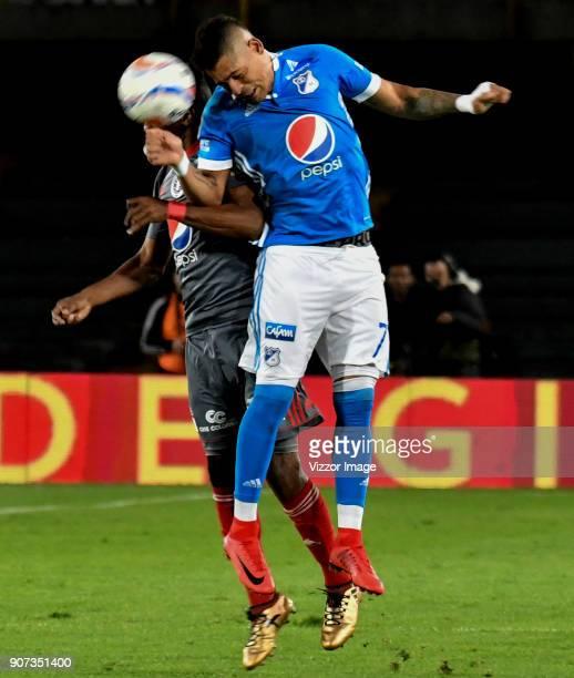 Ayron del Valle of Millonarios heads the ball over Ivan Velez of America de Cali during the friendly match between Millonarios and America de Cali as...
