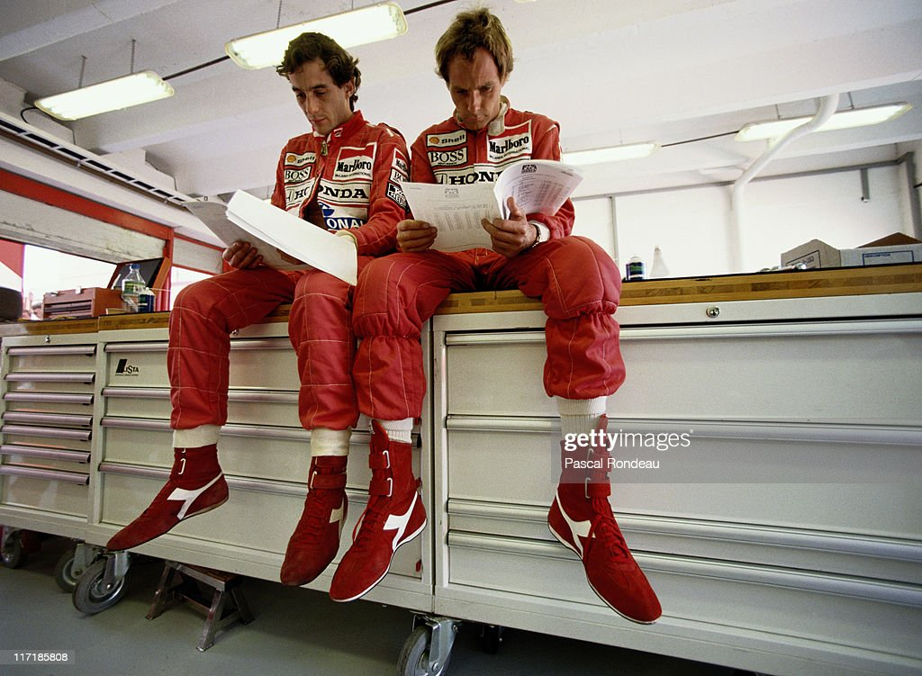 Ayrton Senna (left), driver of the #27 Honda Marlboro McLaren McLaren MP4-5B Honda 3.5 V10 checks the technical data with team mate Gerhard Berger during practice for the Hungarian Grand Prix on 11th August 1990 at the Hungaroring Circuit, Budapest, Hungary.