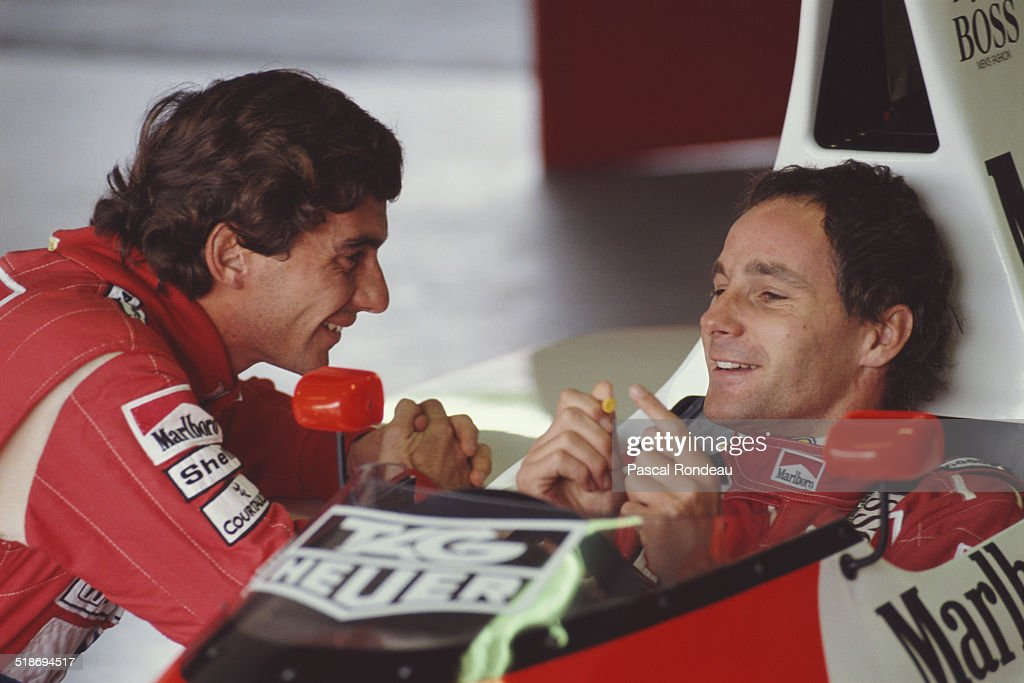 Ayrton Senna, driver of the McLaren-Honda MP4/5B shares a funny joke with team mate Gerhard Berger ( in car) during pre season testing 1st February 1990 at the Autodromo Enzo e Dino Ferrari in Imola, San Marino.