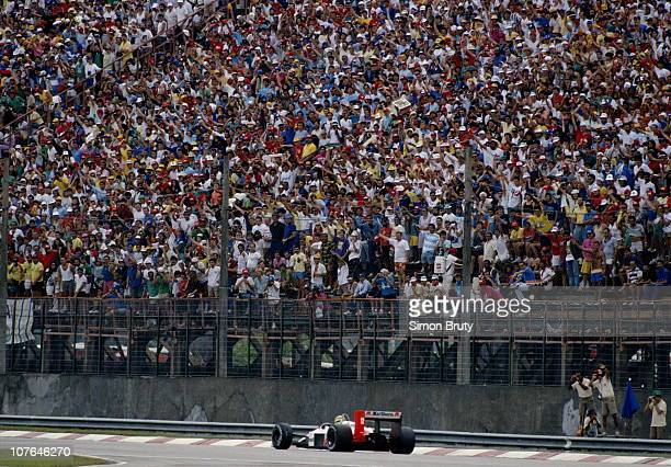Ayrton Senna drives the Honda Marlboro McLaren MP44 Honda 15 V6T passed his adoring fans who salute him during the Brazilian Grand Prix on 3rd March...