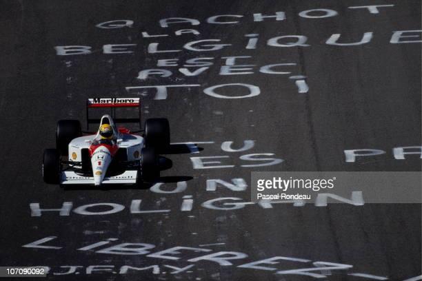 Ayrton Senna drives the Honda Marlboro McLaren-Honda MP4/6 over graffiti on the track supporting jailed driver Bertrand Gachot during the Belgian...