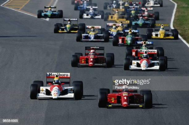 Ayrton Senna driving the Marlboro McLarenHonda MP4/5 and Alain Prost in the Scuderia Ferrari 641 lead the field at the start of the Japanese Grand...