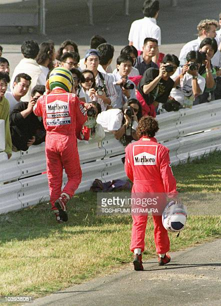 Ayrton Senna of Brazil and Alain Prost of France walk towards their pit 21 October 1990 after they crashed in the first turn right after the start
