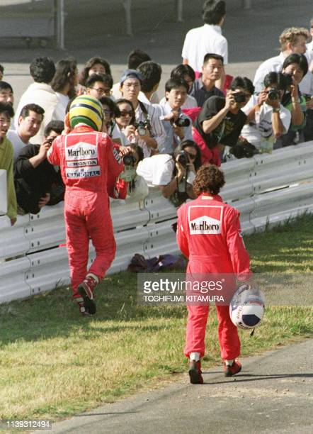Ayrton Senna of Brazil and Alain Prost of France walk towards their pit 21 October 1990 after they crashed in the first turn right after the start.