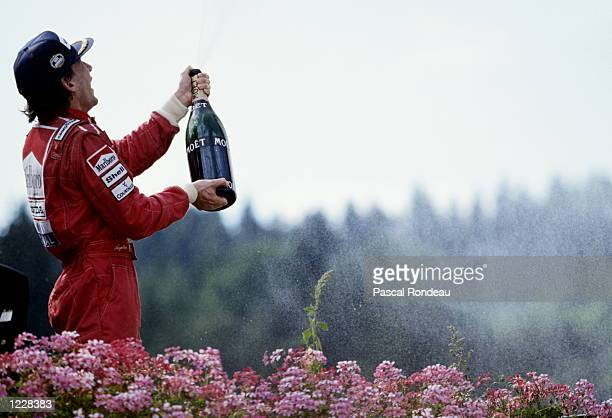 Ayrton Senna of Brazil driver of the Honda Marlboro McLarenHonda MP4/6 sprays champagne as he celebrates winning the Belgian Grand Prix on 25 August...