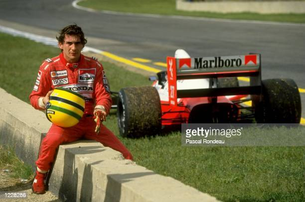 Ayrton Senna of Brazil sits on a wall next to his McLaren Honda during the Spanish Grand Prix at the Jerez circuit in Spain Senna retired from the...