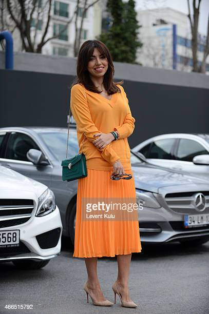 Aysegul Uluc wearing sunglasses by And Other Storm, shoes by Christian Louboutin and a hang bag and wristband by Bvlgari during Mercedes Benz Fashion...