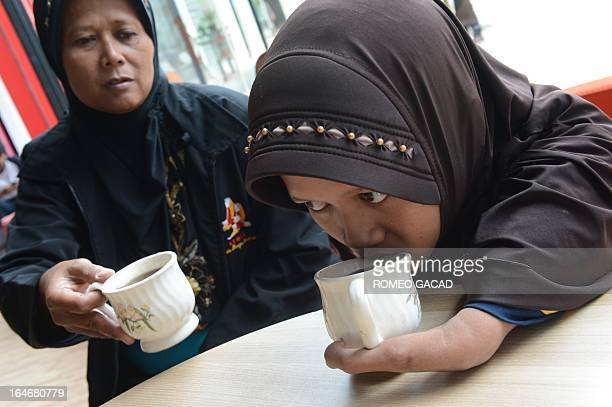 Ayu a 22 year old handicapped Indonesian drinks coffee beside her mother Triyatmi after a batik pattern demonstration in Jakarta on March 26 2013 Ayu...