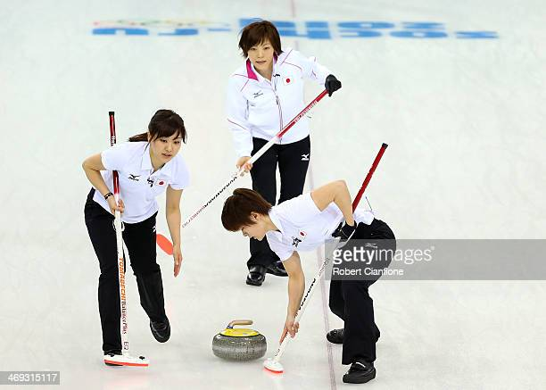 Ayumi Ogasawara of Japan looks on as Chinami Yoshida and Michiko Tomabechi sweep the ice during the Curling Women's Round Robin match between Japan...