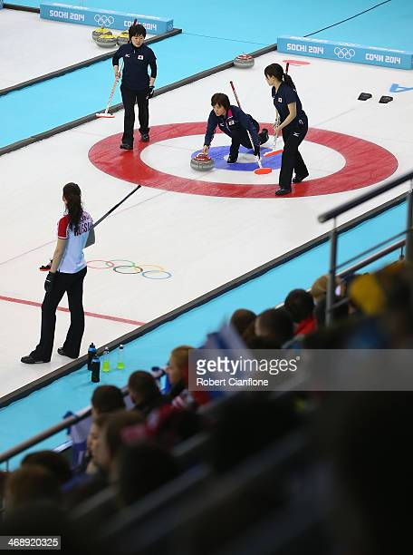 Ayumi Ogsawara of Japan delivers the stone while Michiko Tomabechi and Chinami Yoshida prepare to sweep during Curling Women's Round Robin match...