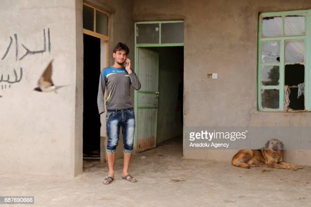 Azad, one of the two siblings who was accused of theft and whose right hand was cut off by Daesh, plays with a dog in Ninova, Iraq on May 23, 2017....