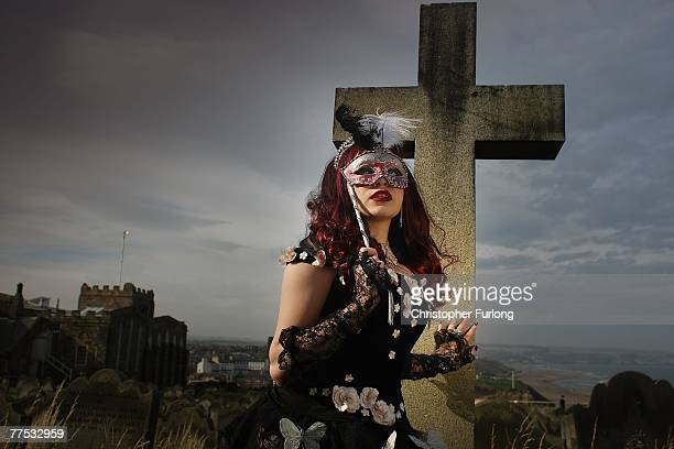 Azadeh dressed in Goth style poses beside a gravestone in a churchyard for photographers during Whitby Gothic Weekend on 27 October 2007 in Whitby...