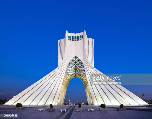 azadi tower illuminated at late dusk in tehran, iran - tehran stock pictures, royalty-free photos & images