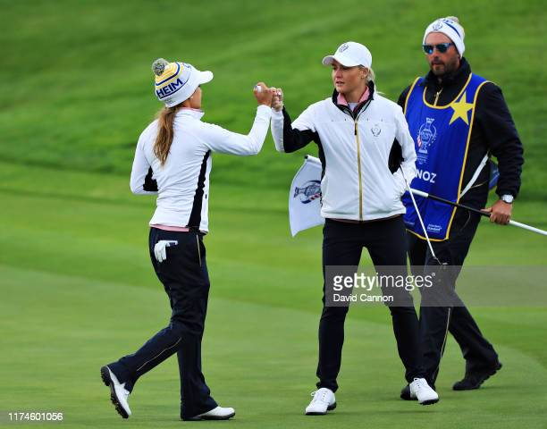 Azahara Munoz and Charley Hull of Team Europe react to a putt on the second green during Day 2 of the Solheim Cup at Gleneagles on September 14, 2019...