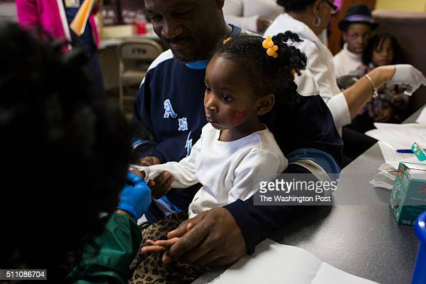 Azariah Hawthorne is held by her grandfather Nile Hawthorne Sr as she gets her blood lead levels tested at Carriage Town Ministries in Flint Mich on...