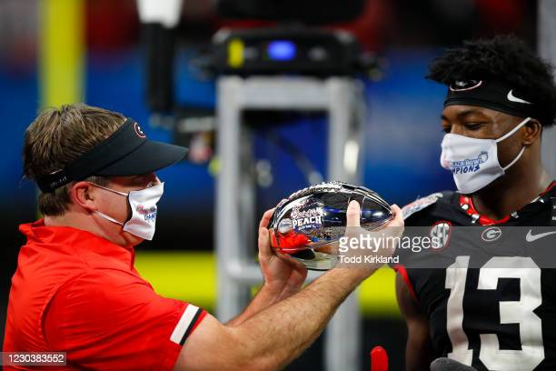 Azeez Ojulari of the Georgia Bulldogs celebrates with head coach Kirby Smart at the conclusion of the Chick-fil-A Peach Bowl against the Cincinnati...