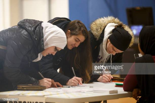 Azemina Hodzic prepares to vote with her two daughters, Amra Hodzic and Lejla Hodzic at a polling place at Cromie Elementary School on March 10, 2020...