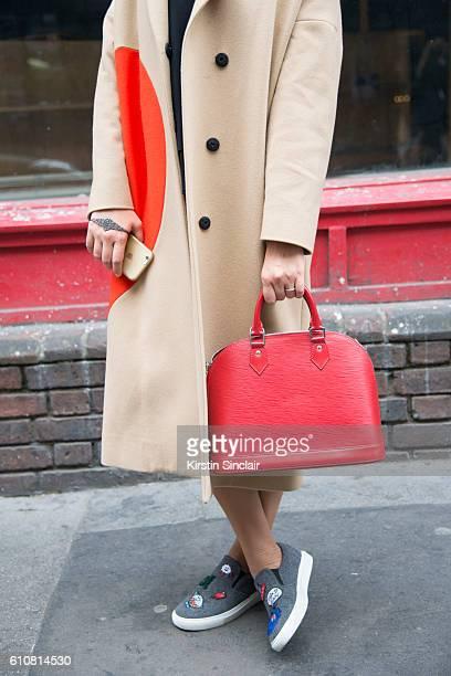 Azerbaijan fashion editor Leyla Ahmadova wears an MSGM coat Academie top and skirt Miro Micante shoes Gaydamak jewelry and Louis Vuitton bag on day 5...