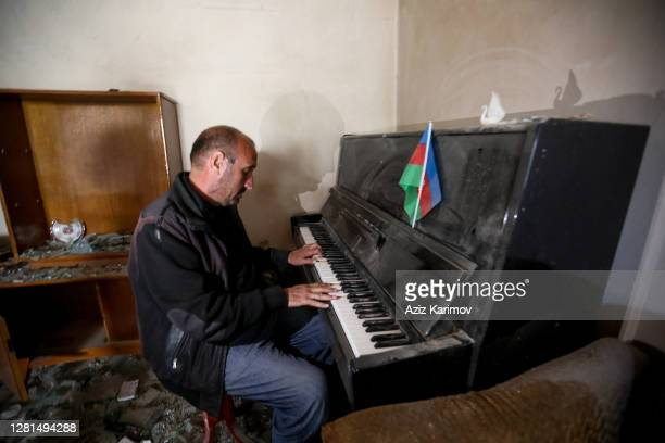 Azerbaijani citizen Konul Abbasov plays piano at his completely destroyed house after an attack on October 21, 2020 in Ganja, The fighting between...