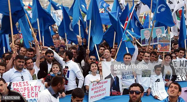 Azerbaijani opposition supporters hold posters and flags during a protest rally in Baku on April 22 2012 Azerbaijani opposition parties rally against...